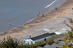 Langland Bay, Swansea, UK, 30th March 2020.<br />A swimmer and people out walking at Langland Bay near Swansea today as government warnings continue to ask people to stay at home due to the Coronavirus outbreak in the UK, except for daily exercise.