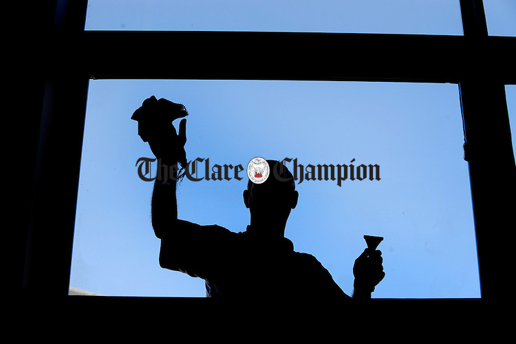 A man puts the finishing touches to the hall windows on the first day of school in the new Ballyea NS. Photograph by John Kelly.