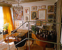 A simple metal staircase leads down to a living room with a grand piano and a wall entirely covered in a fascinating collection of modernist works of art