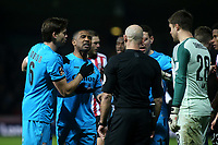 Barnet's Andre Boucaud (second from left) has words with referee, Roger East during Brentford vs Barnet, Emirates FA Cup Football at Griffin Park on 5th February 2019