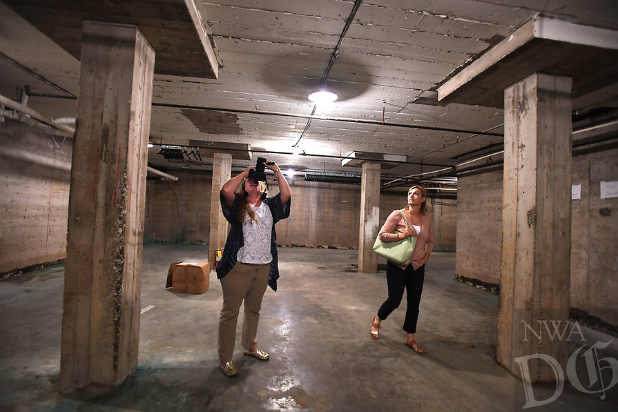 NWA Democrat-Gazette/J.T. WAMPLER  Sarah King, marketing and outreach with Specialized Real Estate Group (LEFT) photographs the ceiling while Kaitlyn Fondano, construction manager with Specialized watches Thursday August 8, 2019 at the former Farmers Cooperative building on Martin Luther King Jr. Blvd. in Fayetteville.<br /><br />Specialized Real Estate Group bought the property this year and plans to put in more than 200 apartments and renovate the existing properties for a mix of restaurants, entertainment, office and retail space.