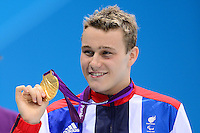 PICTURE BY ALEX BROADWAY /SWPIX.COM - 2012 London Paralympic Games - Day Seven - Swimming, Aquatic Centre, Olympic Park, London, England - 05/09/12 - Oliver Hynd of Great Britain poses with his Gold Medal after victory in the Men's 200m Individual Medley SM8 Final.