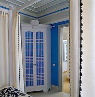 A small wardrobe in one corner of the guest bedroom has been painted blue and white in keeping with the decoration of the room