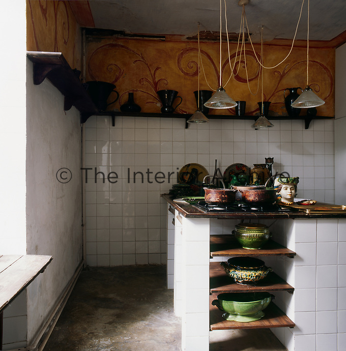 A rustic kitchen with a yellow painted wall above a white ceramic tiled wall. Lamps on long flexes hang above a hob on a tiled unit. Several Vallauris pottery bowls are displayed on wooden shelves below.
