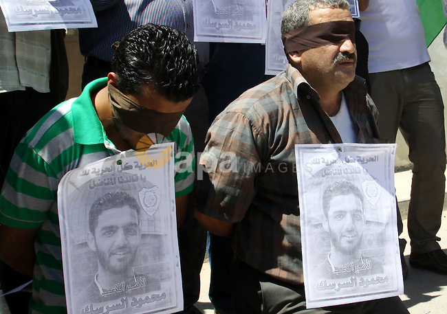 Palestinian protestors hold pictures of Palestinian prisoners Mahmoud Al-Sarsak and Akram al-Rikhawi, whose are still refusing food for 86 days after a deal was made to end a mass prisoner hunger strike, during a demonstration in their support, In front  the Red Cross in the West Bank, city of Nablus on 12 June, 2012. Photo by Nedal Shtieh
