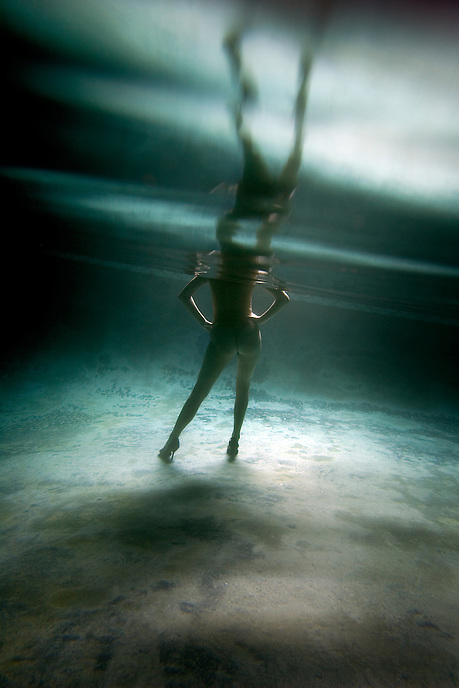 A nude woman stands in a pool. A female underwater fashion model.