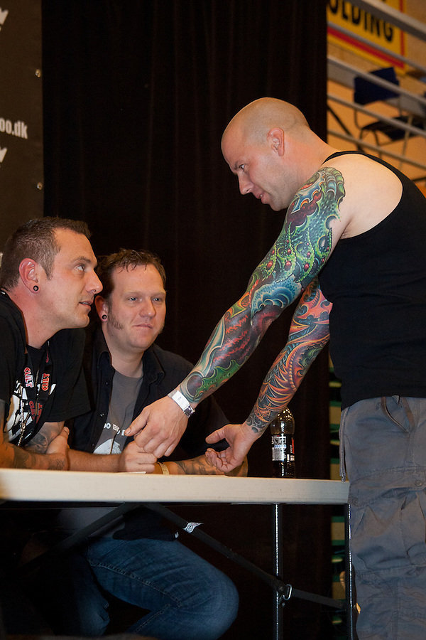 Tattoo Convention in Kolding 2011. Arranged by BodyMod.dk<br /> Man showing his colorful sleeves to the judges.