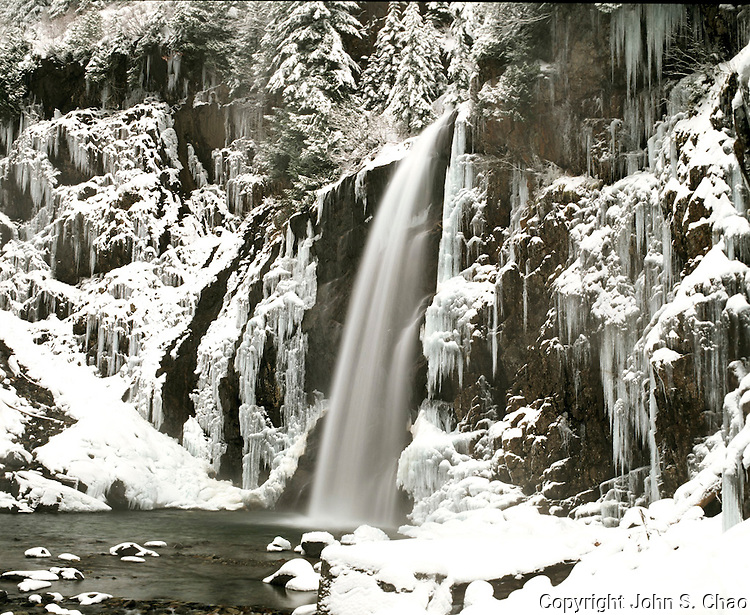 Franklin Falls, flanked by large, long icicles, flowing in wintertime. Snoqualmie Pass area, Washington State.....Photographed on 6X7 format Velvia 50 film.