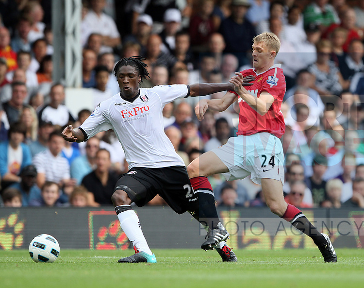 Fulham's Dickson Etuhu tussles with Manchester United's Darren Fletcher