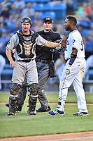 Asheville Tourists first baseman Luis Castro (31) is being held back by catcher Arden Pabst (25) and home plate umpire Dillon Wilson after being hit in the head by a pitch during a game against the West Virginia Power at McCormick Field on May 10, 2017 in Asheville, North Carolina. The Tourists defeated the Power 4-3. (Tony Farlow/Four Seam Images)
