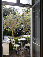 The drawing room French windows lead to a secluded town garden with a paved patio seating area.