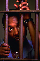 African American prisoner looking through the bars of his prison cell. Tennessee State Prison.