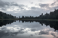 Dawn reflections of clouds in Lake Matheson, Westland Tai Poutini National Park, West Coast, UNESCO World Heritage Area, South Westland, New Zealand, NZ