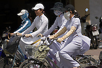 Girls in their traditional uniforms cycle away from their school in Nha Trang, Vietnam. Many girls cover their heads, faces and arms in order to avoid being tanned by the strong sun.