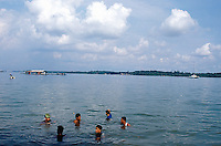 Singapore. Pulau Ubin island. A group of men take a bath on a sunny saturday in the south china sea. A fisherman is on his small motor boat and a sailing boat is anchored.  © 2001 Didier Ruef