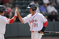 Shortstop Javier Guerra (31) of the Greenville Drive is congratulated after scoring a run in a game against the Hagerstorn Suns on Thursday, May 7, 2015, at Fluor Field at the West End in Greenville, South Carolina. Guerra is the No. 13 prospect of the Boston Red Sox, according to Baseball America. Greenville won, 4-0. (Tom Priddy/Four Seam Images)