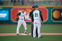 Fort Wayne TinCaps manager Anthony Contreras (10) argues a call with umpire Thomas Burrell as base runner Jawuan Harris (2) looks on during a Midwest League game against the Peoria Chiefs on July 17, 2019 at Parkview Field in Fort Wayne, Indiana.  Fort Wayne defeated Peoria 6-2.  (Mike Janes/Four Seam Images)