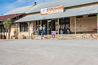 This is a capture of the Terlingua Trading Post as customer come out of the store as the guy plays his guitar on the front porch.