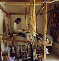 A local man stands at his loom weaving richly coloured textiles