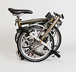 Brompton Folding Bicycle, 2016; Designed by Andrew Ritchie (English, b. 1947); Manufactured by Brompton Bicycle (Brentford, England); Assembled bent, brazed, and lacquered tubular steel (frame) and titanium (mudguards), synthetic (saddle), molded rubber and Kevlar (tires); open: 57.2 × 55.2 × 147.3 cm (22 1/2 in. × 21 3/4 in. × 58 in.), folded: 56.4 × 54.6 × 24.9 cm (22 3/16 × 21 1/2 × 9 13/16 in.); Gift of Brompton Bicycle, 2016-19-1; Photo:  Matt Flynn © Smithsonian Institution