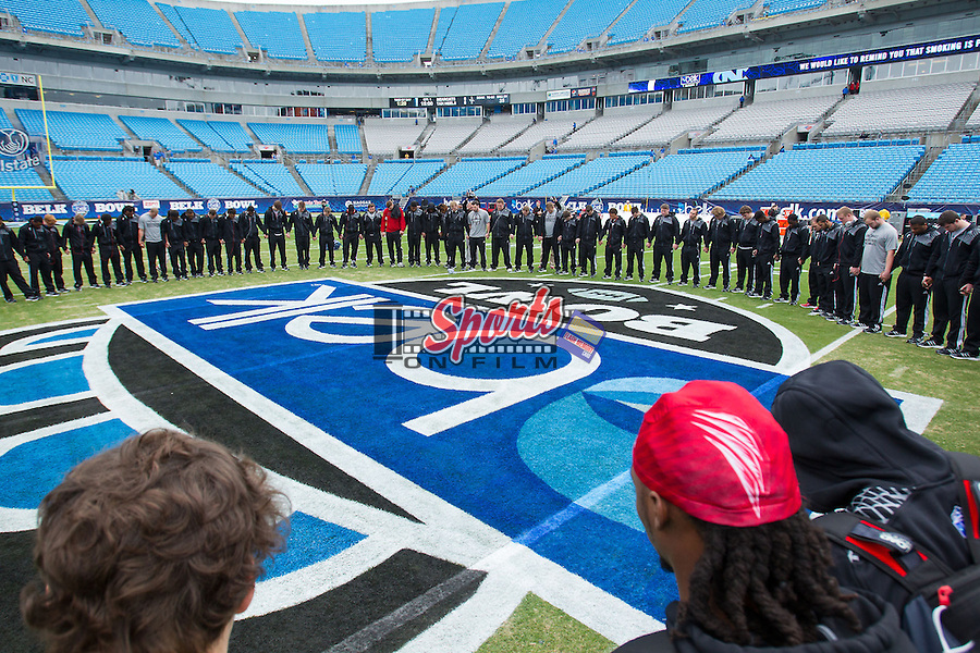 The Cincinnati Bearcats hold hands for a prayer at midfield prior to the Belk Bowl against the North Carolina Tar Heels at Bank of America Stadium on December 28, 2013 in Charlotte, North Carolina.  The Tar Heels defeated the Bearcats 39-17.   (Brian Westerholt/Sports On Film)
