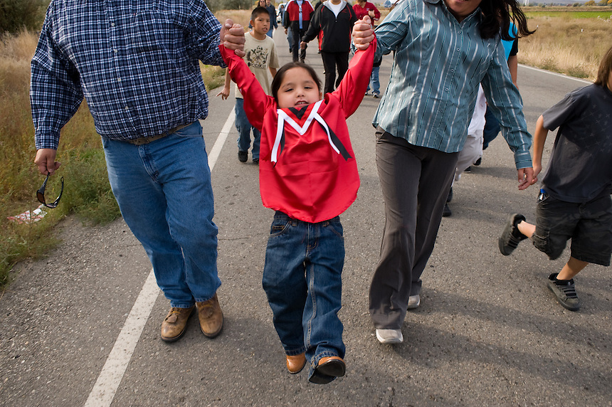 Young student Jerrad Friday Jr., 3, gets a swing from parents Jerrad Friday Sr., left, and mom Tara Coffee during a march from the local charter school to the site of a new language immersion school on the Wind River Indian Reservation in central Wyoming, Friday, Oct. 3, 2008. Northern Arapaho tribal leaders hope the inauguration of the larger new Arapaho Language Lodge immersion school at the reservation will help kids find a better cultural identity and strengthen them better succeed in education. (Kevin Moloney for the New York Times)
