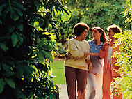 Three women laugh while enjoying an afternoon together at a botanical garden