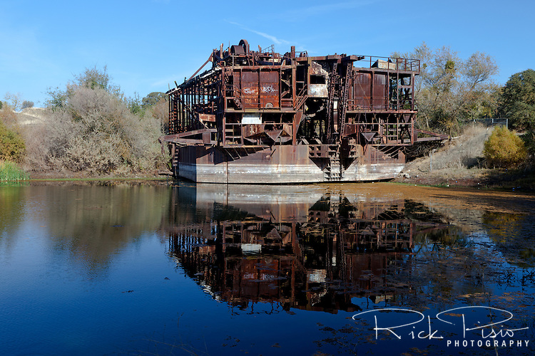 Constructed in 1933 at a cost of $543,148 the Tuolomne Gold Dredge has sat idle since 1951. Located near the former mining town of La Grange, in California's Gold Country, the dredge weighed over 2500 tons and floated on its own self-created pond of water. The dredge's boom consisted of 120 buckets weighing 4000 pounds each that extended 70 feet below the waters surface. The total amound of gold recovered by the dredge is not known. The dredge is registered as historic landmark #1971000208.