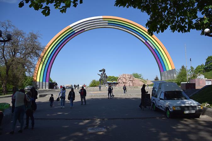 ESC Vorbericht. Ein paar Tage vor dem ESC in der Innenstadt von Kiew:<br />Der Bogen im Hintergrund sollte zum ESC in Regenbogenfarben bemalt werden, entsprechend dem diesj&auml;hrigen ESC-Motto: &quot;Celebrate Diversity&quot;. Neuer Name: &quot;Bogen der Vielfalt.&quot; Die ukrainischen Nationalisten attackierten allerdings die Bemalungsarbeiten. Sie sehen in dem Regenbogen das Symbol von Lesben- und Schwulenbewegung und protestieren dagegen. Der B&uuml;rgermeister Vitali Klitschko erkl&auml;rte schlie&szlig;lich, die grauen noch nicht angestrichenen Stellen w&uuml;rde man zum Beginn von ESC noch mit einem ukrainischen Ornament bemalen.