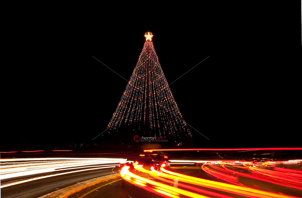 Cars light streaks whizzing past the illuminated Zilker Park Christmas Tree