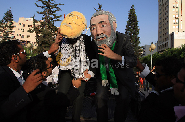 Two Palestinians wearing masks representing Palestinian President Mahmoud Abbas, left, and Head of Gaza's Hamas government Ismail Haniyeh during a demonstration calling for Palestinian unity, in Gaza City on July1, 2009. Palestinians said Tuesday the rival Hamas and Fatah movements ended their latest round of reconciliation talks in Cairo without reaching a deal.  photo by Wissam Nassar