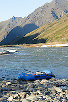 A raft gives scale to the ice, water and mountainsalong the Kongakut River, in Alaska's Arctic National Wildlife Refuge.