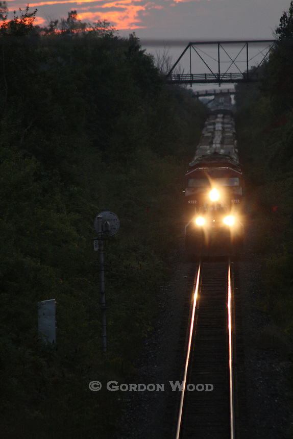 Freight Train at Sunset Under Truss Bridge