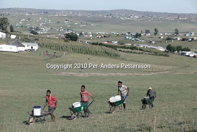 QUNU,SOUTH AFRICA - APRIL 2: Youth push wheelbarrows with water collected at a water sourcein the village of Qunu, where Nelson Mandela grew upon April 2, 2010, in Qunu, South Africa. Mr. Mandela was born in Mvezo, about 32 kilometers from here and Qunu and its surroundings is the area where he learned about life including his traditional manhood ceremony. Mr. Mandela was born in 1918, he served as a president of South Africa from 1994-1999, when he retired. Before that he was the leader of the armed wing of ANC and was convicted of sabotage among other crimes and served 27 years in prison, many of them on Robben Island, outside Cape Town. Qunu has a museum and Mr. Mandela has a big house where he and his family spends time while in the area. (Photo by Per-Anders Pettersson)