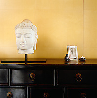 A Buddha's head sits on the sideboard