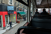 Empty shop on Kilburn High Road, London, from a bus window.