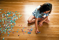 Eight year old girl working on a jigsaw puzzle.