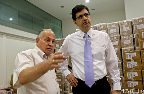 Portrait of VivaCell- Armenia CEO Ralph Yirikian talks to a worker in front of packed SIM cards at his office headquarters in Yerevan, the capital of Armenia.