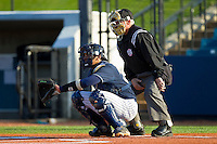 UNCG Spartans catcher Cambric Moye (30) warms up his pitcher as home plate umpire Tom Haight looks on during the game against the Georgia Southern Eagles at UNCG Baseball Stadium on March 29, 2013 in Greensboro, North Carolina.  The Spartans defeated the Eagles 5-4.  (Brian Westerholt/Four Seam Images)