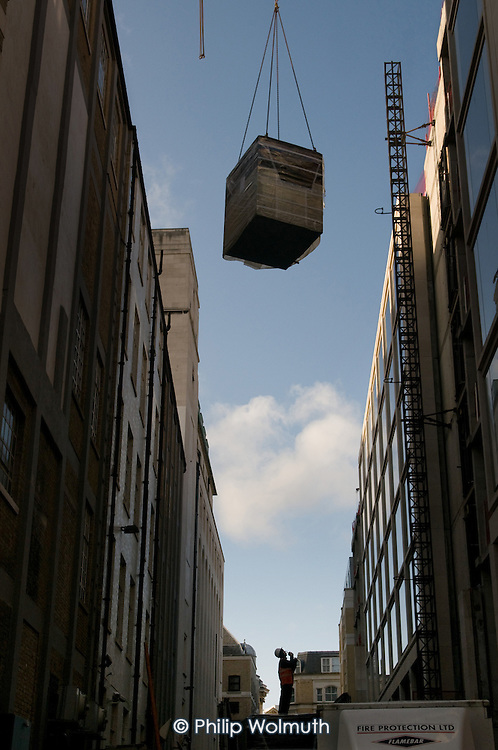 A construction worker watches as a crane lifts a load on a building site in the City of London.