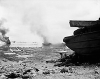 An amphibious tractor burns on the beach as Marines take shelter under a duck.  Peleliu, September 1944.  Pfc. John J. Smith. (Marine Corps)<br /> Exact Date Shot Unknown<br /> NARA FILE #:  127-N-95249<br /> WAR &amp; CONFLICT BOOK #:  1178