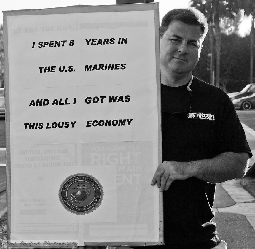 "A man holds a sign reading ""I spent 8 yeras in the U.S. Marines and all I got was this lousy economy"".  Taken at the Occupy Orange County - Irvine camp on Halloween."