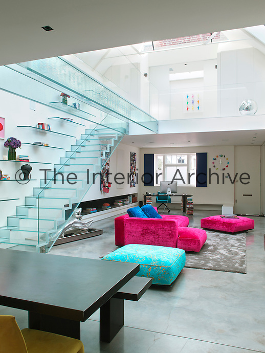 The blue tint in the glass, against the bright white walls of the living room, makes the staircase and bridge appear like individual pieces of sculpture hovering above the space