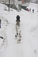 During a snow storm, Shane Goosen leaves at the Tokotna checkpoint after returning earlier to drop a dog.  2005 Iditarod Trail Sled Dog Race.
