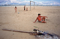 A family relaxes with freshly-caught fish and a game of soccer on a sandbar at the junction of the Rio Negro and Rio Solimões (Amazon) near Manaus, Brazil, Sunday, Jan. 8, 2006. As the rainy season approaches, the sand playground will disappear under meters of water. (Kevin Moloney for the New York Times)