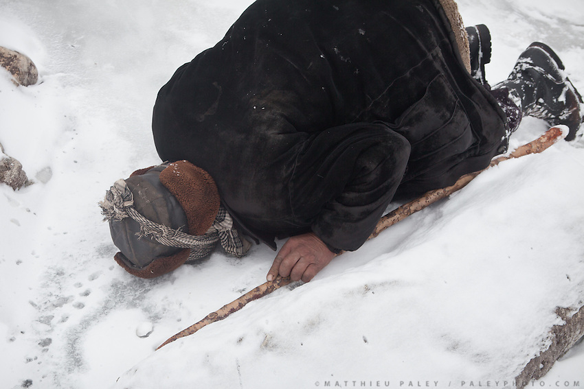 "Shukr Ali, our caravan leader, takes a drink of water from a hole in the ice..From Zan Kuk to Zardibar (""yellow door""). ..Trekking back down from the Little Pamir, with yak caravan, over the frozen Wakhan river."