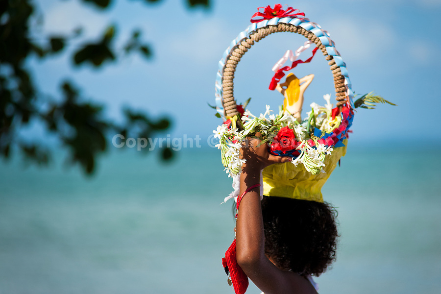 A Candomblé worshipper carries a flower basket during the ritual procession in honor to Yemanjá, the goddess of the sea, in Amoreiras, Bahia, Brazil, 3 February 2012. Yemanjá, originally from the ancient Yoruba mythology, is one of the most popular ?orixás?, the deities from the Afro-Brazilian religion of Candomblé. Every year on February 3rd, hundreds of Yemanjá devotees participate in a colorful celebration in her honor. Faithful, usually dressed in the traditional white, gather at the beach on Itaparica island to leave offerings for their goddess. Gifts for Yemanjá include flowers, perfumes or jewelry. Dancing in the circle and singing ancestral Yoruba prayers, sometimes the followers enter into a trance and become possessed by the spirits. Although Yemanjá is widely worshipped throughout Latin America, including south of Brazil, Uruguay, Cuba or Haiti, the most popular cult is maintained in Bahia, Brazil.