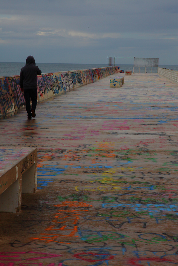 The dock in the old part of the town, in Bari, with a person taken from behind that is walking towards the sea. The dock is colorful, because of its paintings and writings, and there is a suggestive open gate at its end. Digitally Improved Photo.