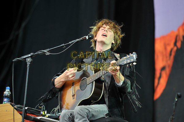 Blaine Harrison of The Mystery Jets.performing on Day 2 at Reading Festival, Reading, England. .25th August 2012.on stage in concert live gig performance performing music half length black fringed jacket guitar singing .CAP/MAR.© Martin Harris/Capital Pictures.