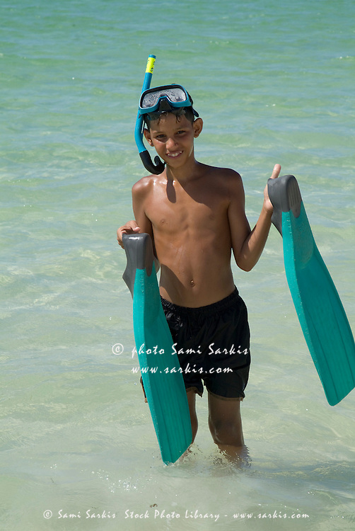 Cuban boy holding swimfins at the beach, Cayo Jutias, Cuba.